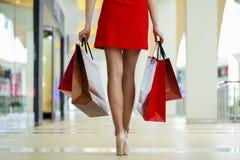 Jambes de robe rouge de port shopaholic tout en portant plusieurs pape photos stock