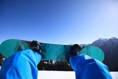 Jambes de snowboarding en montagnes Image libre de droits