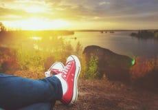 Jambes de voyageur se reposant sur la falaise Concep de voyage et de liberté Images stock