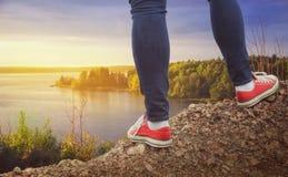 Jambes de voyageur se tenant sur la falaise Conce de voyage et de liberté Photos stock