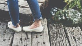 Jambes des blues-jean d'habillement de femmes et des chaussures blanches Images stock