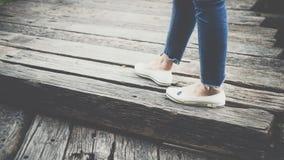 Jambes des blues-jean d'habillement de femmes et des chaussures blanches Image stock