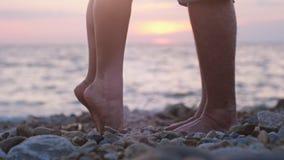 Jambes des couples dans l'amour pendant la date près de la mer sur la plage pendant le beau coucher du soleil Image libre de droits