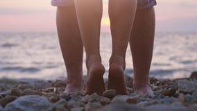 Jambes des couples dans l'amour près de la mer sur la plage pendant le beau coucher du soleil Photos libres de droits