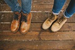 Jambes des couples dans les bottes sur le plancher en bois dehors Images libres de droits