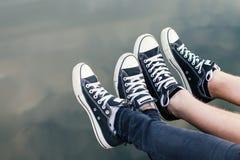 Jambes des couples se reposant au-dessus de l'eau images stock