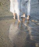 Jambes des couples sur la plage de sable Photographie stock libre de droits