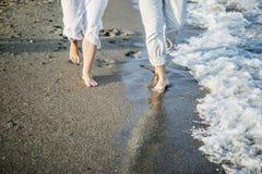 Jambes des couples sur la plage de sable Image stock