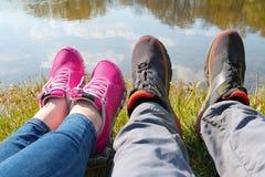 Jambes des jeunes dans des espadrilles dans la perspective de l'eau Photographie stock