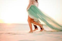 Jambes des jeunes mariés marchant nu-pieds dans le désert au coucher du soleil Cl Photos libres de droits