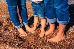Jambes du ` s d'enfants et pieds de parents La famille marche le long de la plage Photographie stock libre de droits