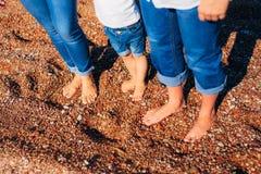 Jambes du ` s d'enfants et pieds de parents La famille marche le long de la plage Image stock