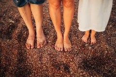 Jambes du ` s d'enfants et pieds de parents La famille marche le long de la plage Photos libres de droits