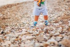 Jambes du ` s d'enfants et pieds de parents La famille marche le long de la plage Images stock