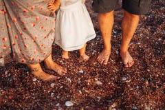 Jambes du ` s d'enfants et pieds de parents La famille marche le long de la plage Photo libre de droits