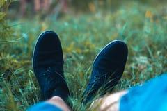 Jambes du ` s d'hommes dans des espadrilles en parc sur l'herbe Photos stock