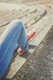 Jambes du ` s de femme dans blues-jean et espadrilles rouges de toile se reposant sur un banc Images stock