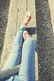 Jambes du ` s de femme dans blues-jean et espadrilles rouges de toile se reposant sur un banc Image libre de droits
