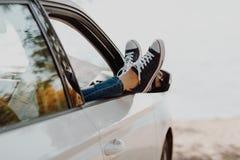 Jambes du ` s de femme dans des espadrilles dans la voiture de fenêtre avec la carte de route Fille dans des jeans dans la voitur Photographie stock