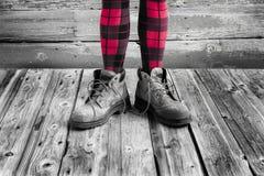Jambes du ` s de femme des genoux portant vers le bas les collants rouges et noirs et les grandes bottes photos libres de droits