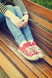 Jambes du ` s de femme utilisant les espadrilles rouges de toile Images stock