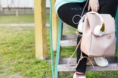 Jambes du ` s de femmes dans des jeans et des espadrilles, sac à dos, des écouteurs et téléphone intelligent Image libre de droits