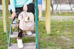Jambes du ` s de femmes dans des jeans et des espadrilles, sac à dos, des écouteurs et téléphone intelligent Photos stock