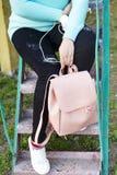 Jambes du ` s de femmes dans des jeans et des espadrilles, sac à dos, des écouteurs et téléphone intelligent Photographie stock libre de droits
