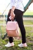 Jambes du ` s de femmes dans des jeans et des espadrilles, sac à dos et téléphone intelligent Photos libres de droits