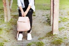 Jambes du ` s de femmes dans des jeans et des espadrilles, sac à dos et téléphone intelligent Photo stock