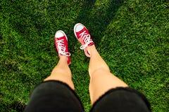 Jambes du ` s de fille se tenant sur l'herbe en parc D'en haut Photographie stock