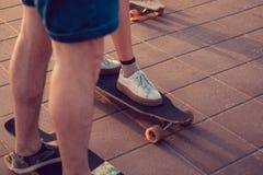 Jambes du ` s de patineur sur des longboards Images stock