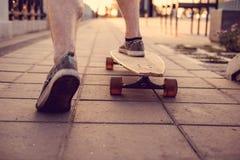 Jambes du ` s de patineur sur Longboard Photographie stock libre de droits