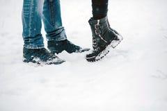 Jambes embrassant des couples se tenant sur la neige Photo stock