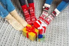 Jambes en chaussettes et cadeaux de Noël tricotés photographie stock