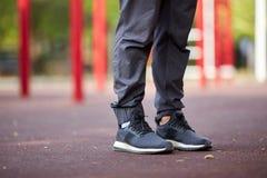 Jambes en gros plan du ` s d'homme dans des pantalons et des chaussures de sports sur un fond brouillé Concept de vêtements de sp Photo stock