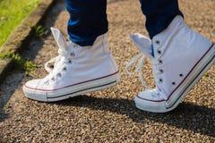 Jambes en gros plan du ` s de fille dans des espadrilles blanches sur le fond d'asphalte Image stock