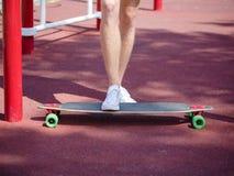 Jambes en gros plan sur une planche à roulettes Équipez la position sur un longboard à la mode sur un fond brouillé de parc Conce Photo stock