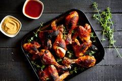 Jambes et ailes de poulet grillées avec de la sauce barbecue et la moutarde photos stock
