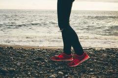 Jambes et espadrilles sur la plage de mer Photos stock