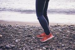 Jambes et espadrilles sur la plage de mer Images stock