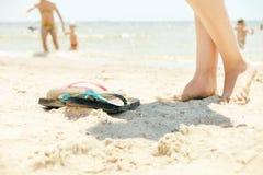 Jambes et pantoufles femelles de plage sur le sable blanc Image stock
