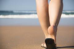 Jambes et pieds d'une fille marchant vers la mer images stock