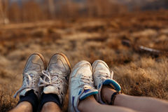 Jambes et pieds de couples de hippie au coucher du soleil en montagnes, l'espace pour t image libre de droits