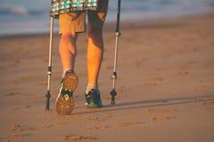Jambes et poteaux de dame âgée nordique de marcheur sur la plage photos stock