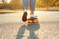 Jambes faisantes de la planche à roulettes au parc de patin Beau temps avec le soleil Image libre de droits