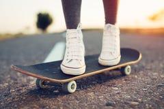 Jambes faisantes de la planche à roulettes de femme à la rue de lever de soleil Photo stock
