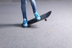 Jambes faisantes de la planche à roulettes de femme au skatepark a de lever de soleil Photo libre de droits