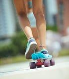 Jambes faisantes de la planche à roulettes de femme sur la planche à roulettes Photo libre de droits