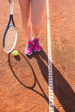 Jambes femelles avec la raquette de tennis Photo libre de droits